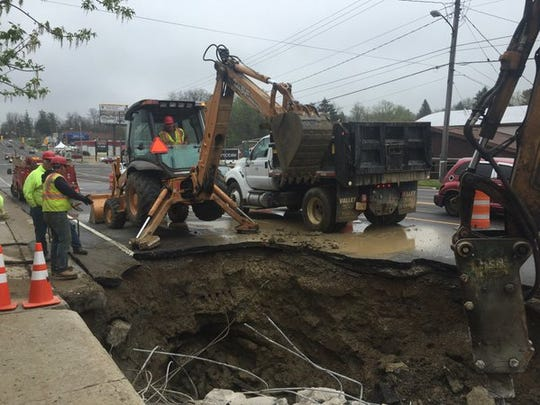 Crews work to repair a water main break on Park Avenue West near Trimble Road Friday.