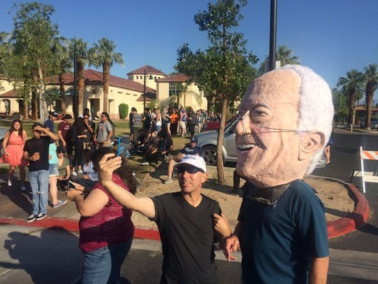 A Bernie Sanders supporter wears a paper-mache head at the senator's rally in Cathedral City.