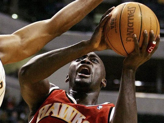 Atlanta Hawks forward Dion Glover right puts up a shot against Indiana Pacers forward Ron Mercer during the second quarter of a preseason game in Indianapolis Saturday Oct. 12 2002.