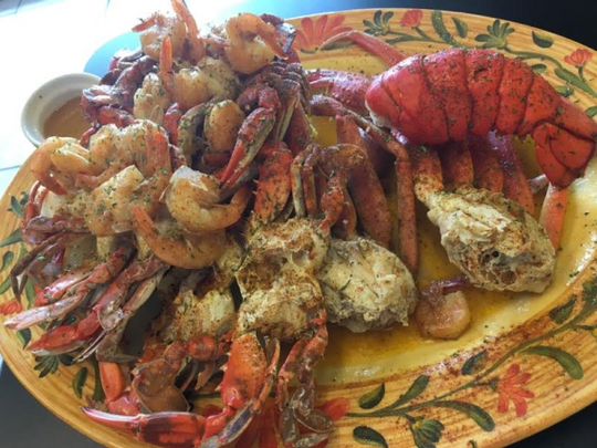 One Love's ultimate platter was a steaming bowl piled high with snow crab legs, shrimp, a lobster tail, blue crabs and double portion each of boiled eggs, pork sausage, ears of corn and a large halved potato all smothered in buttery, garlicky seasoning.
