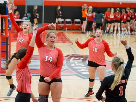 The Lady Knights cheer on a point made during a volleyball