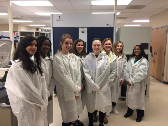 Students from Menomonee Falls High School wear lab coats as they tour Wisconsin Diagnostic Laboratories.