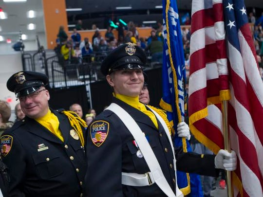 Oshkosh Police Officer Bonnell carries the American Flag during the National Anthem at the start of a Wisconsin Herd game March 9 at the Menominee Nation Arena.