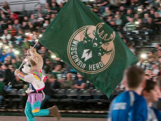 The Wisconsin Herd mascot runs the flag onto the court at the start of a March 21 game at Menominee Nation Arena in Oshkosh.