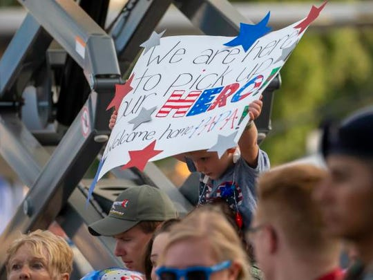 People bring homemade signs for the welcome home veterans returning from an Old Glory Honor Flight during Friday's AirVenture on the EAA grounds July 27, 2018.