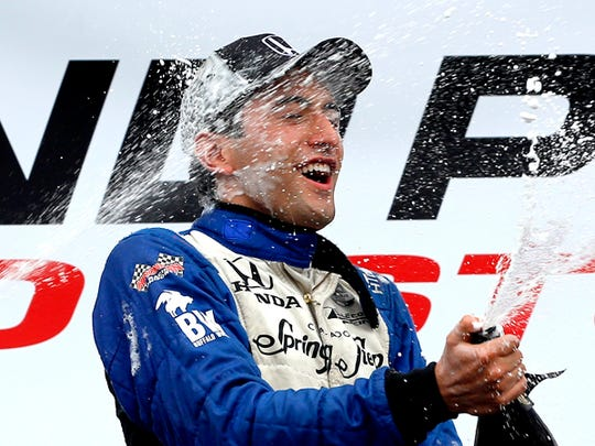 Carlos Huetas, of Colombia, is sprayed with champaign after winning the first of two IndyCar Grand Prix of Houston auto races Saturday, June 28, 2014, in Houston. (AP Photo/David J. Phillip)