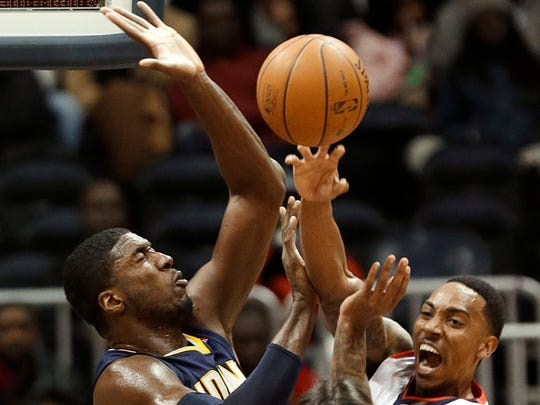 Atlanta Hawks point guard Jeff Teague, right, passes as Indiana Pacers center Roy Hibbert (55) defends during the first half of an NBA basketball game Wednesday, Jan. 8, 2014, in Atlanta, THe Hawks won 97-87.(AP Photo/John Bazemore)