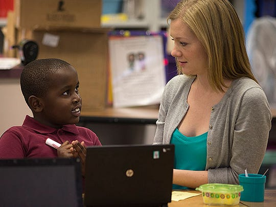 Second-grader Mohamed Sugow gets one-on-one attention from student teacher Victoria Garrison during class at David Crockett School. The school is in the Balsz School District, which is seeking a $2.1 million override.