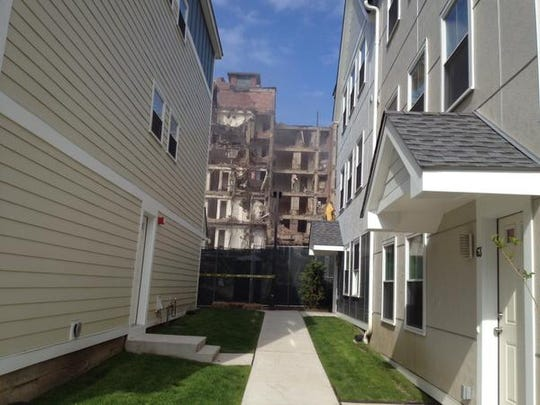 Townhouses flank a new walkway at Heritage Homes in New Rochelle, a replacement for Hartley Homes which is being torn down and visible in the background.