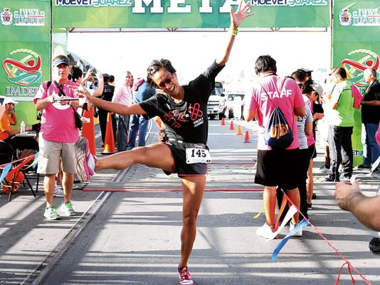 Abbey Diaz celebrates after being one of the first women to finish the U.S.-Mexico 10K Saturday at the top of the Paso del Norte bridge.