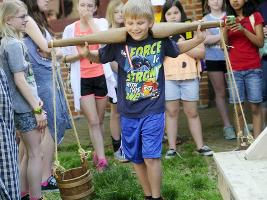 Colton Bryson, a fifth-grader at  Mazie Gable Elementary School, carries two buckets connected to a yoke as he gets a idea of colonial period chores during a class trip to the Colonial Complex earlier this month.