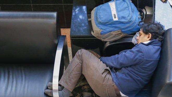 A stranded air traveler sleeps with his luggage at Hartsfield-Jackson Atlanta International Airport on Jan. 27, 2015.