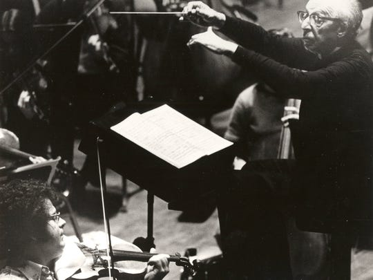 Composer Aaron Copland conducts the Cincinnati Symphony Orchestra with violin soloist Itzhak Perlman (foreground), Jan. 18, 1974.