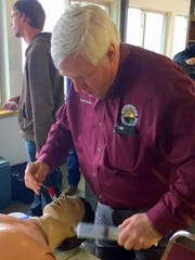 Dave Pearce takes his turn practicing emergency medical measures on a dummy.