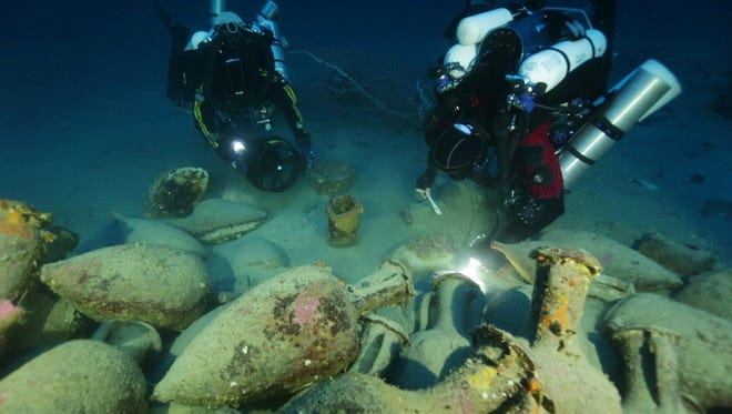A photo provided by Global Underwater Explorers shows divers illuminating Greco-Roman artifacts of a ship that sunk during the Punic Wars between 218-201 B.C.