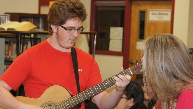 After a student in Uganda sang for Deming students, Adam Lindberg reciprocated by playing guitar for them during Wednesday's Skype session.