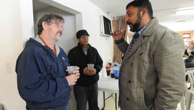 Craig Zychal, left of Milford talks with Usman Sandhu, president of the Islamic Society of Central Delaware in Felton after their Friday prayer.