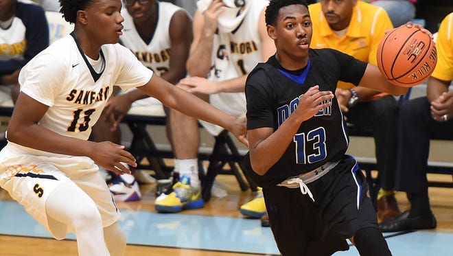 Sanford's Jyare Davis (left) guards Dover's Troy Scott at Slam Dunk to the Beach on Dec. 27 at Cape Henlopen. Sanford has moved up to No. 1 in The News Journal's boys basketball rankings.