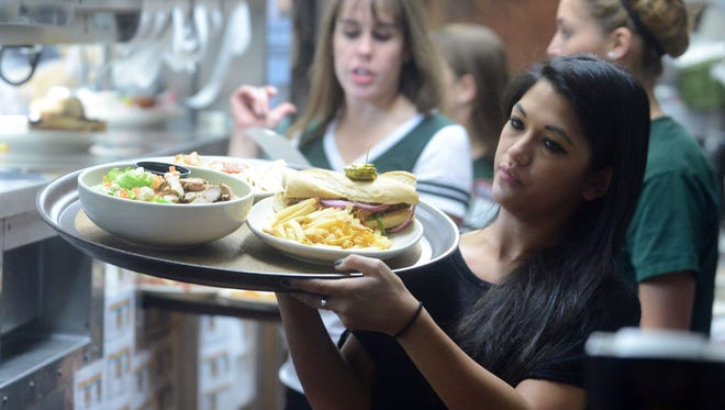 Waitress, Kelsee Palencia, carries a tray of food out from the kitchen at CB & Potts.