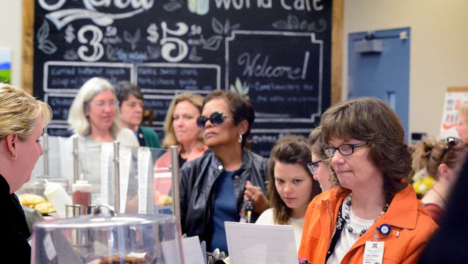 A crowd packs Healthy World Cafe during the restaurant's official downtown opening Monday, April 6, 2015. The pay-how-you-can restaurant announced its closing today. Bill Kalina photo