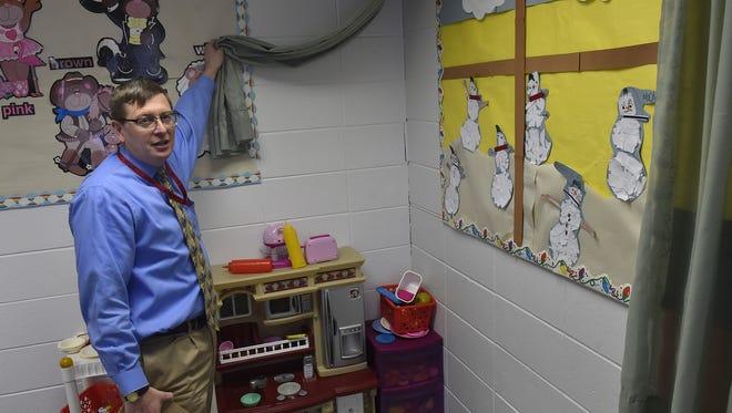 Sevastopol School Superintendent Kyle Luedtke points out cinder block cracks hidden behind a false curtain at the school.