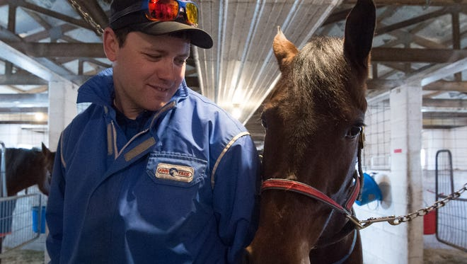 Steven Nason of Freedom, New Hampshire, with Geremel Hanover, a standardbred horse, before heading out for an exercise session at Track View Farm in Hartly.