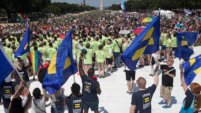 Marchers gather on the National Mall with the Washington Monument in the background during the Equality March for Unity and Pride in Washington, on Sunday, June 11, 2017.