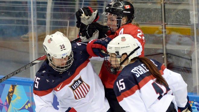 USA defenseman Anne Schleper (15) and forward Alex Carpenter (25) combine to hit Canada forward Hayley Wickenheiser (22) in a preliminary-round game.