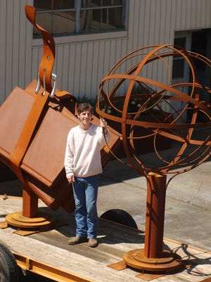 Willy Ferguson poses between two of his sculptures  in Staunton, Va., on April 17, 2002.