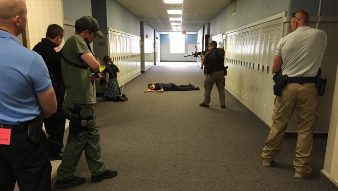 Law enforcement officers confront a woman pretending to be an armed shooter during an emergency drill Friday at Richmond High School.