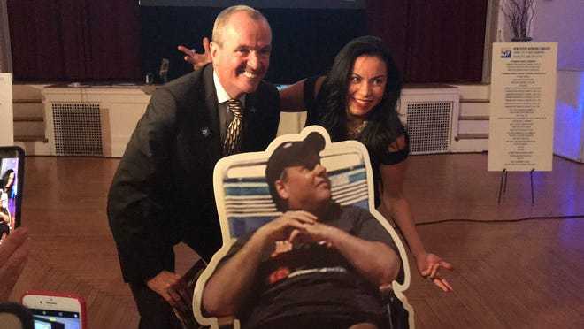 Gov.-elect Phil Murphy and Analilia Mejia of the New Jersey Working Families Alliance stand behind a cutout of Gov. Chris Christie.