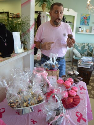 Mark Rodolico, owner of Mark's at the Pointe Salon & Boutique and a board member of Friends After Diagnosis, holds up a tasty treat during the third annual Pink Bake Sale.
