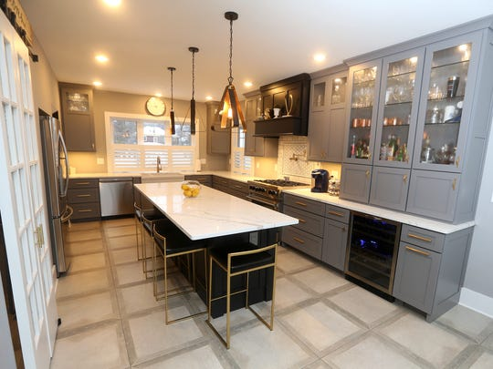 An updated kitchen with lighted cabinets and a microwave that is built into a cabinet.
