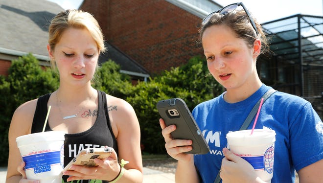 """Shelby Royal, left, and her sister, Elaina Royal, check their smartphones as they play the new Pokémon Go video game Monday, July 11, 2016, in Columbian Park Zoo. """"I downloaded it the day it came out, like four days ago,"""" said Elaina Royal, 19."""