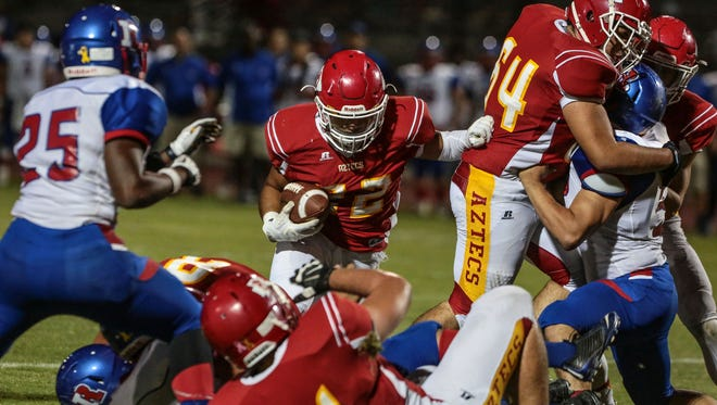 Palm Desert's Manny Sepulveda leaps over Indio defenders and teammates and dives for a touchdown in the first quarter on Friday, November 4, 2016 in Palm Desert.