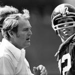 Chuck Noll (left) talks to quarterback Terry Bradshaw during a 1976 game.