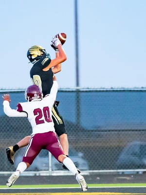 Bushland's Brody Sutterfield catches a touchdown pass as Hereford's Robert Perez defends Friday night in Bushland. The Falcons beat Hereford 56-10 in their home opener.