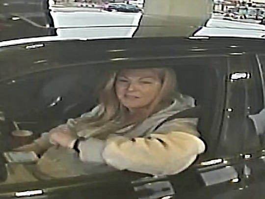A woman is caught on video cashing fraudulent checks