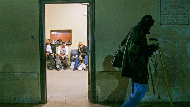 Stuart Carter, 57, walks towards the East Lot while Dee Saafir (from left), 36, Henry Harding, 40 and Kevin Wheeler, 57, sit inside the Men's Overflow Shelter February 4, 2015.  The East Lot is a parking lot that serves as Maricopa County's current solution for emergency shelter. The shelter is set to close at the end of March.