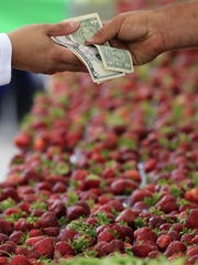 A customer buys fresh strawberries Wednesday at the Farmers Market On Broadway  in Green Bay.