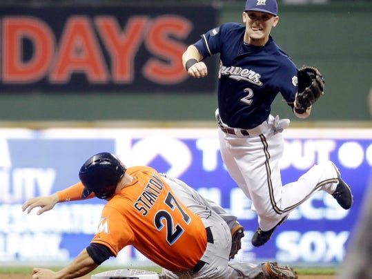 Milwaukee Brewers second baseman Scooter Gennett leaps over Miami Marlins' Giancarlo Stanton while watching his throw on a double play hit into by Marlins' Casey McGehee during the first inning of a baseball game Wednesday, Sept. 10, 2014, in Milwaukee. (AP Photo/Morry Gash)