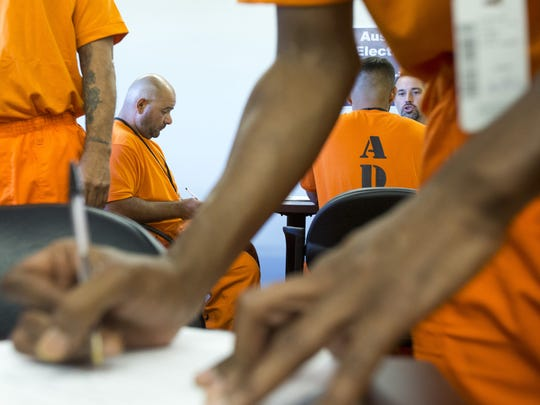 In this file photo, inmates wait for their turn to meet employers to fill out job applications at the Sunrise Employment Center at Lewis Prison.