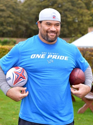 Detroit Lions defensive tackle Haloti Ngata holds a rugby ball and football during practice at The Grove in preparation of the NFL International Series game against the Kansas City Chiefs.
