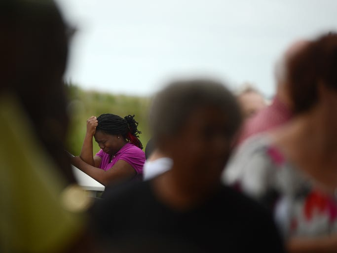 "Onesia Hadley stops to cry as she makes her way to a prayer recovery service on Tuesday, Aug. 12, 2014 for 8-year-old Uvihin ""Ace"" Horton, who drowned on Sunday at Cape Charles Beach. Hadley was one of several family members who attended the service. Horton's body was recovered by rescue workers Tuesday morning."