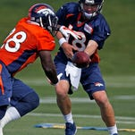 Denver quarterback Peyton Manning hands off to Montee Ball (28) during the first day of NFL football training camp Thursday.