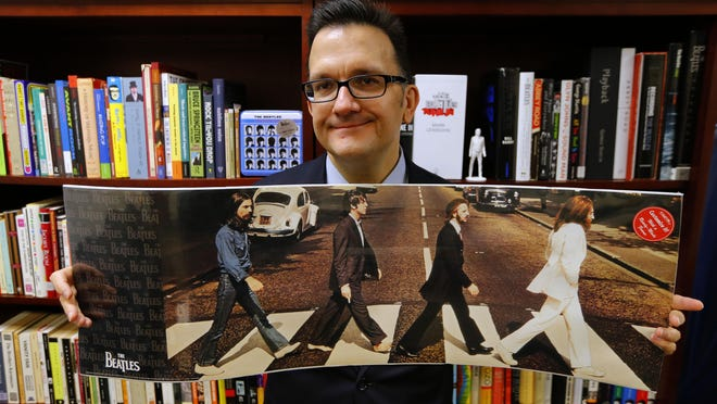 Monmouth University dean Kenneth Womack, a leading scholarly expert on The Beatles, seen with books and memorabilia in his office.