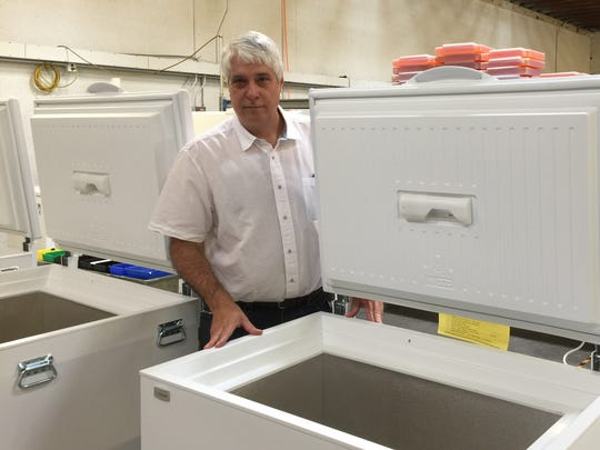 David Bergeron, SunDanzer Refrigeration founder and president, stands next to a vaccine-storage refrigerator at the company's Tucson headquarters.