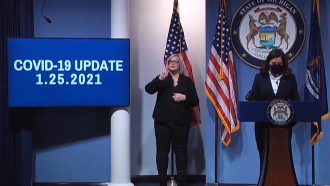 Michigan Gov. Gretchen Whitmer, stands at the podium, with an American Sign Language interpreter behind her, during Monday's press conference. This is a screenshot from the livestream of the program.