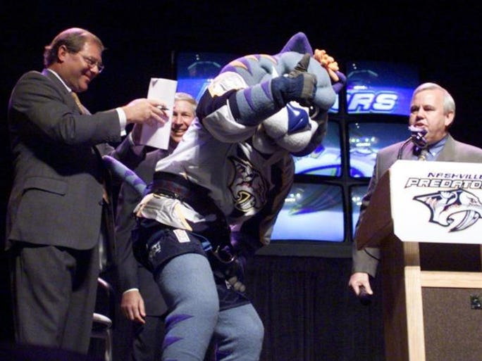 Nashville Predators mascot Gnash, center, offers his back Aug. 4, 1999 as a writing surface for team owner Craig Leopold, left, to sign a contract solidifying the deal renaming the Nashville Arena as the Gaylord Entertainment Center.