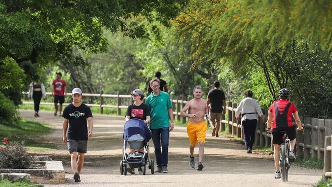 People walk and jog at the Ann and Roy Butler Hike and Bike Trail in downtown Austin in March 2020.